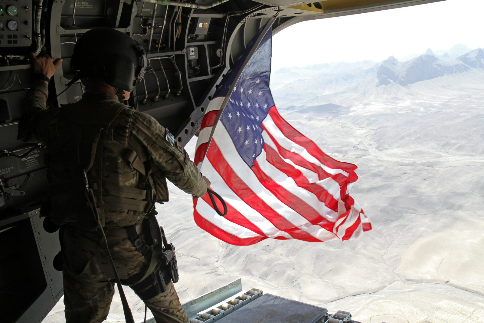 soldier flying U.S. flag from helicopter