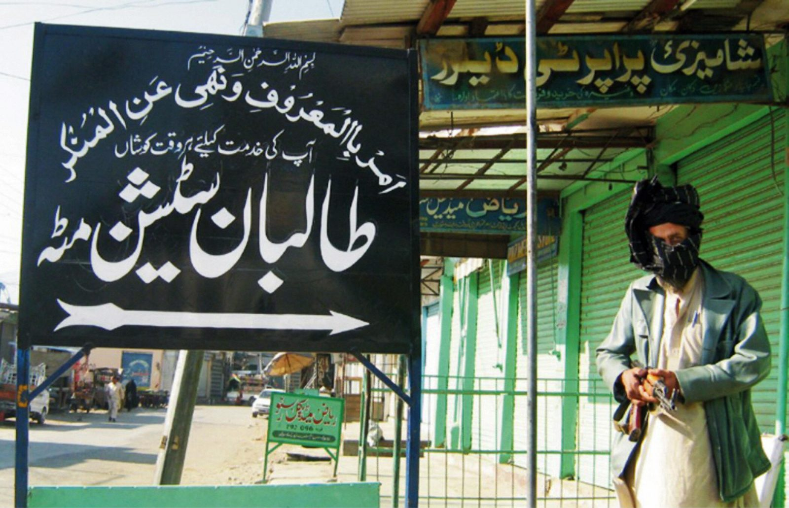 "pro-Taliban militant standing by sign reading ""Taliban Station"""
